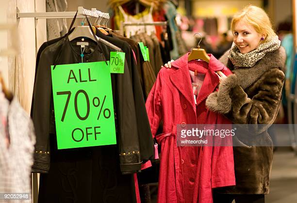 A woman smiling while going through rack of 70% off clothes