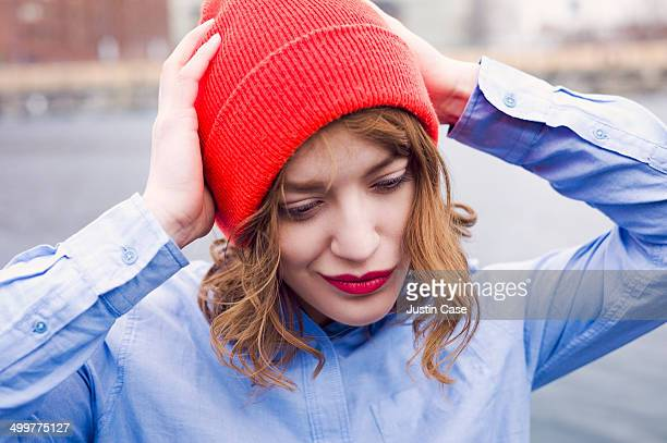 woman smiling while holding her red beany