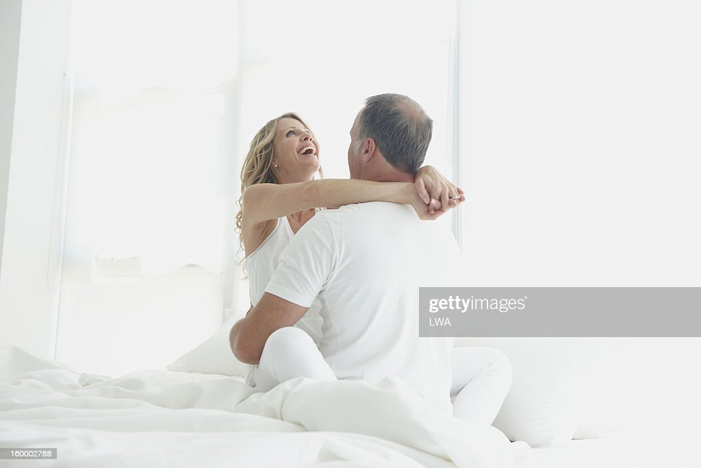 Woman smiling while hugging man : Stock Photo