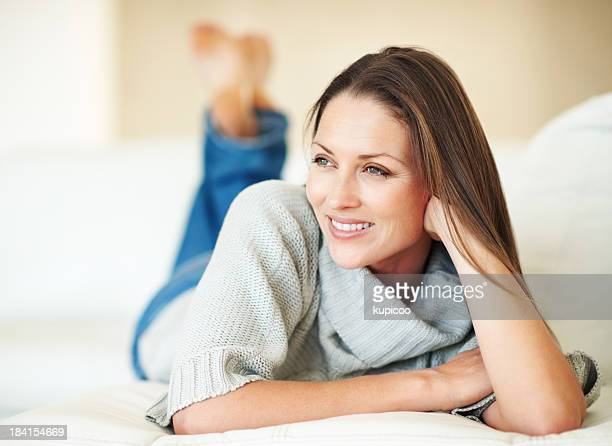 Femme souriant tout en détendant dans un canapé-lit