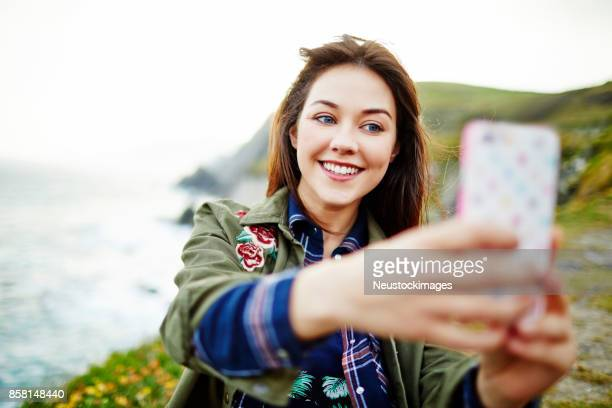 Woman smiling while taking selfie with smart phone on mountain