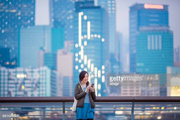 Woman smiling while using smartphone in city