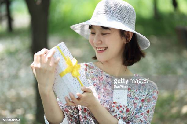 woman smiling while watching a present box