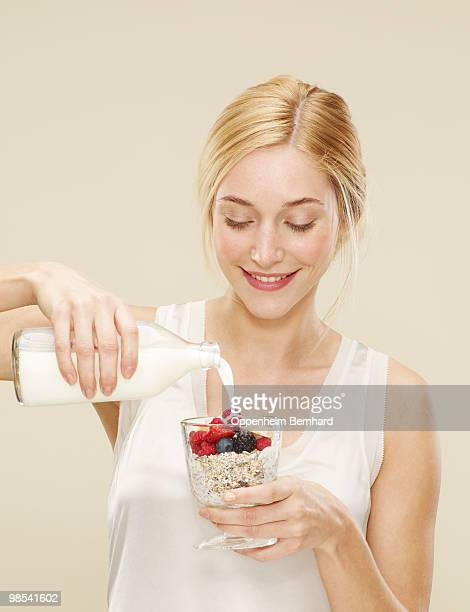 woman smiling whilst pouring milk onto cereal