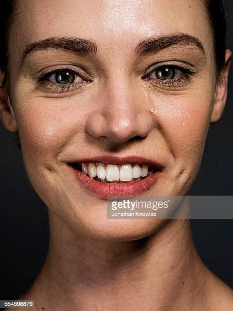 Woman smiling with a tear running down her face