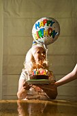 Woman smiling with birthday cake and balloon