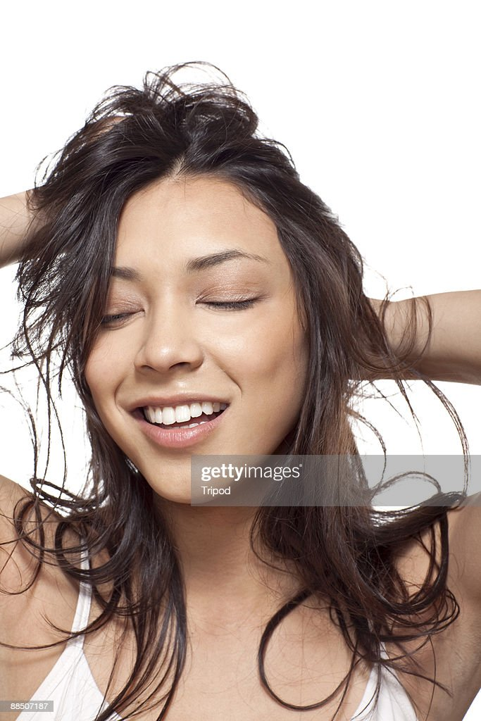 Woman smiling with hands in hair : Stock Photo