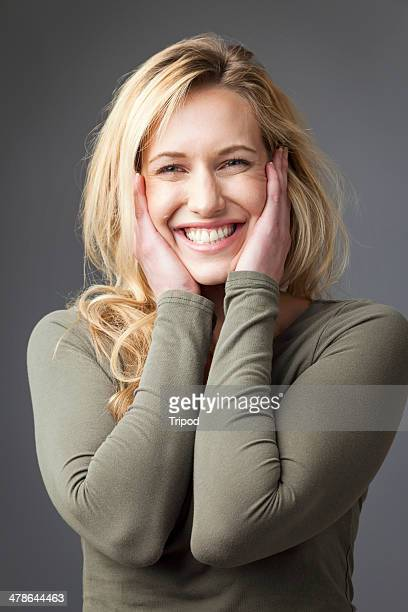 Woman smiling with hands on face