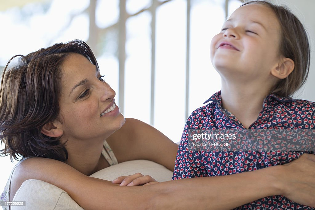 Woman smiling with her daughter at home : Stock Photo