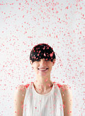 woman smiling with red confetti falling on head