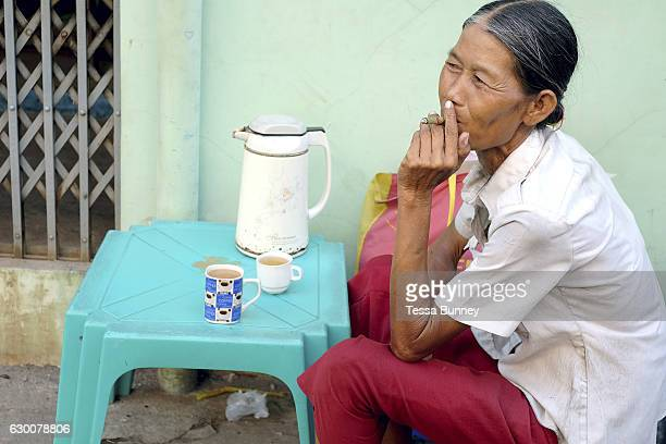 A woman smokes a cheroot at a tea shop on the streets of Yangon on 18th May 2016 in Myanmar