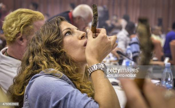 A woman smokes a cigar during the contest for the longest ash during the XVI Havana Cigar Festival in the Cuban capital on February 27 2014 The...