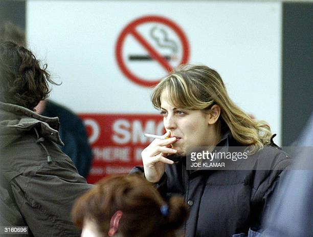 A woman smokes a cigarete in front of a nosmoking sign outside Dublin International airport 30 March 2004 Europe's toughest antismoking law to date...