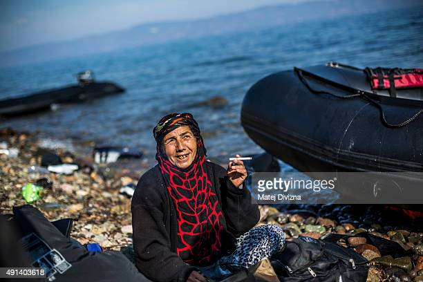 A woman smokes a cigarette after arriving with other refugees and migrants on the shores of the Greek island of Lesbos after crossing the Aegean sea...