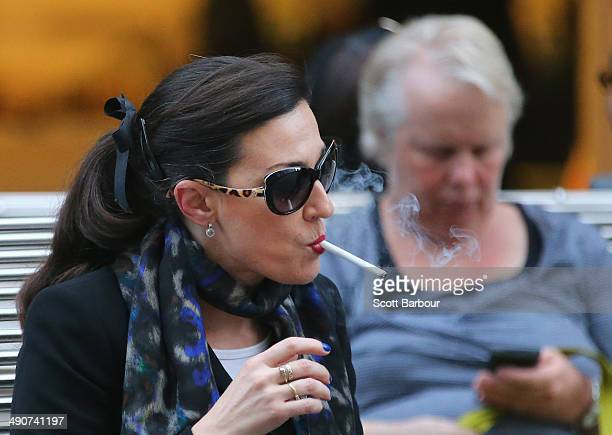 A woman smokes a cigarette in the central business district on May 15 2014 in Melbourne Australia Following a successful smoking ban in the Melbourne...