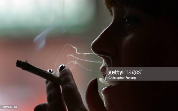 A woman smokes a cigarette of marijuana in an Amsterdam cafe on February 7 2007 in Amsterdam Netherlands The city council in Amsterdam has recently...