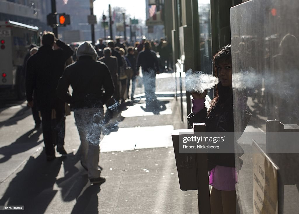 A woman smokes a cigarette on Broadway December 3, 2012 near the New York Stock Exchange in the Manhattan borough of New York.