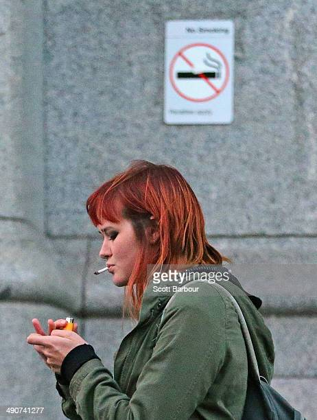 A woman smokes a cigarette outside of Flinders Street Station on May 15 2014 in Melbourne Australia Following a successful smoking ban in the...
