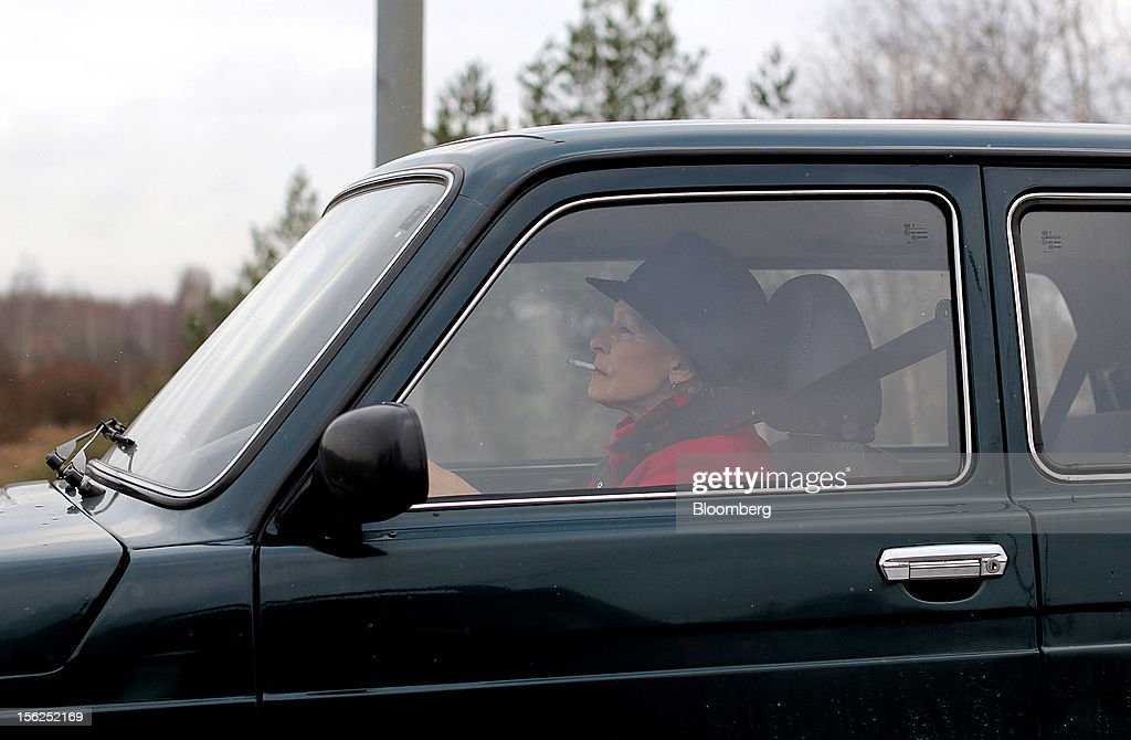 A woman smokes a cigarette whilst driving her automobile in Psarky village, Moscow region, Russia, on Saturday, Nov. 10, 2012. Russia has one of the world's lowest retirement ages, set in 1932 during the Stalin era. Photographer: Andrey Rudakov/Bloomberg via Getty Images