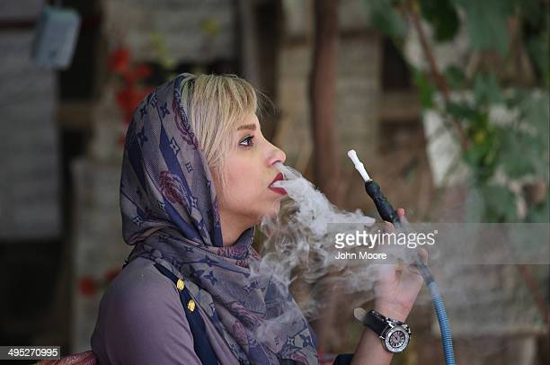 A woman smokes a hookah while visiting a poetry calligraphy workshop on May 29 2014 in Shiraz Iran Shiraz celebrated for more than 2000 years as the...