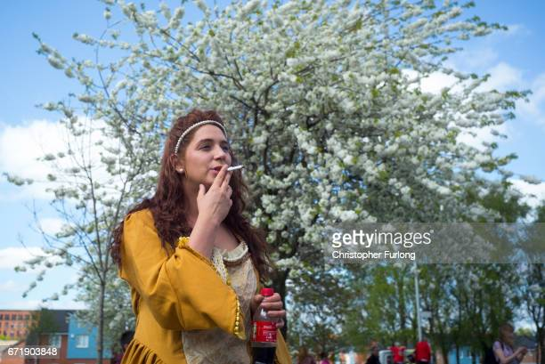 A woman smokes as families and local residents watch the Manchester St George's Day parade through the streets on April 23 2017 in Manchester England...