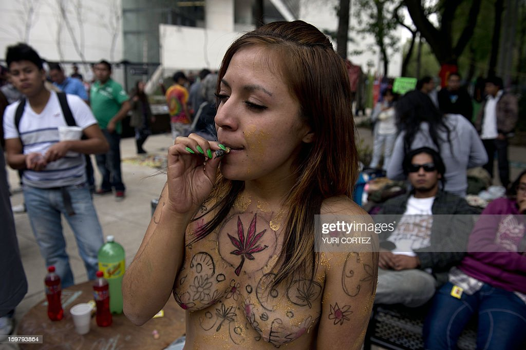 A woman smokes marijuana as she poses with her body painted with marijuana leaves during the 'Marijuana Festival' for its legalization at Luis Pasteur square, in front of building of the Mexican Senate on January 20, 2013 in Mexico City. AFP PHOTO/ Yuri CORTEZ