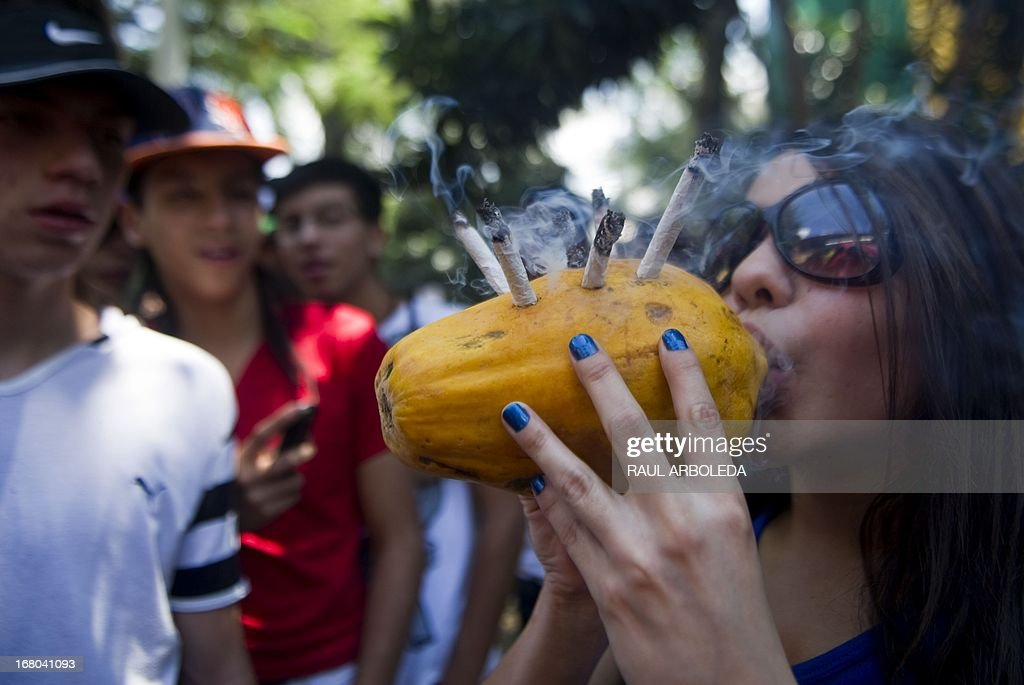 A woman smokes marijuana cigars in a papaya during a march for its decriminalization in Medellin, Antioquia department, Colombia on May 4, 2013, in the framework of the Marijuana World Day. AFP PHOTO/Raul ARBOLEDA