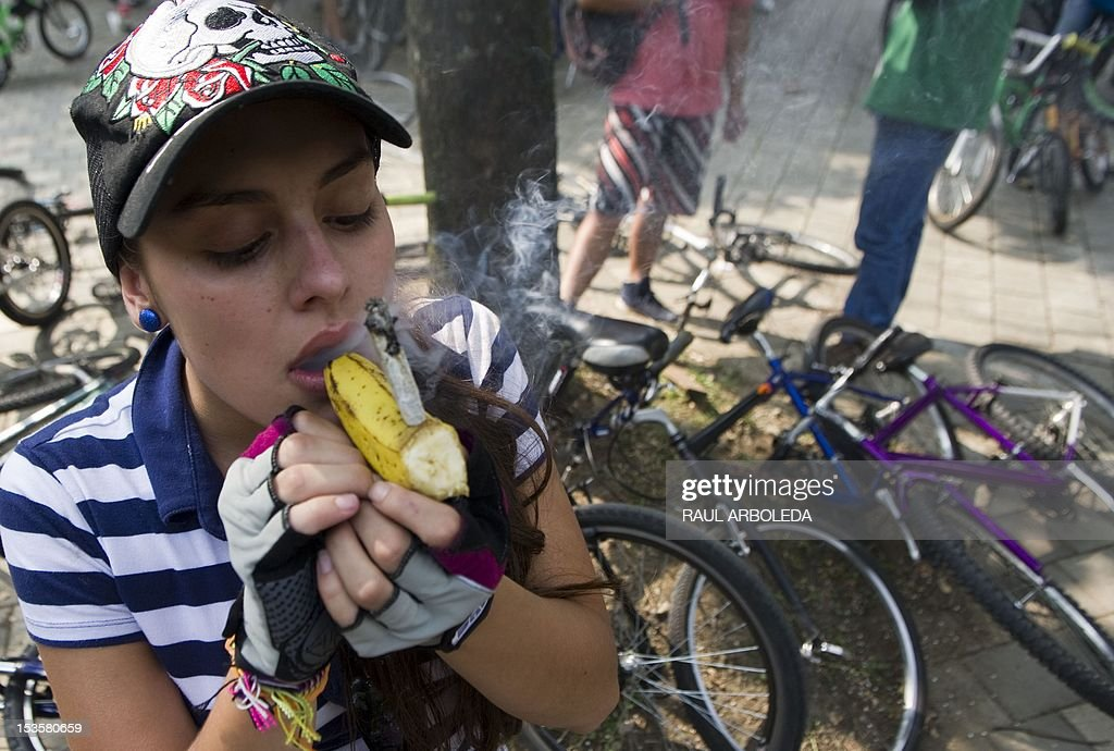 A woman smokes marijuana in a banana during the first world bicycle ride against drug trafficking and in favour of the legalization of self-cultivation of marijuana for medicinal and recreational purposes in Medellin, Antioquia department, Colombia on October 6, 2012. AFP PHOTO/Raul ARBOLEDA