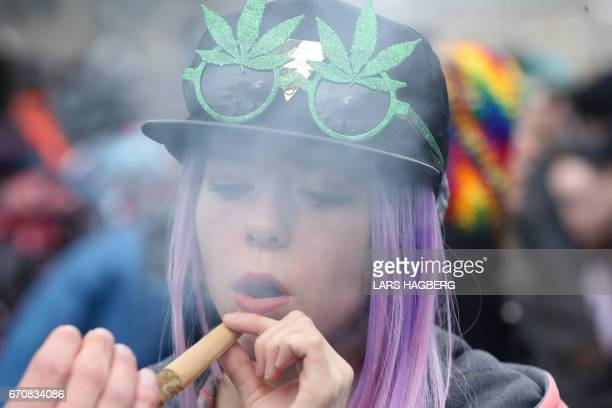 A woman smokes marijuana on Parliament Hill on 4/20 in Ottawa Ontario April 20 2017 Polling released Thursday showed strong support in Canada for a...