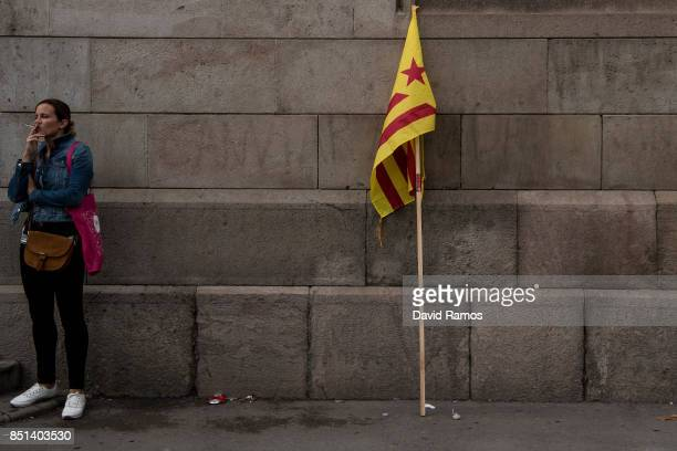 A woman smokes next to a Catalan proindependence flag 'Estelada' outside the rectory of the University of Barcelona during a protest on September 22...
