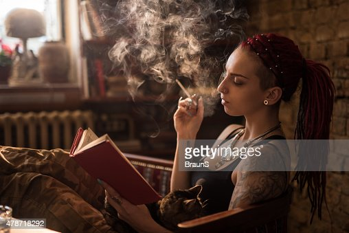 Woman smoking a cigarette while reading a book at home.