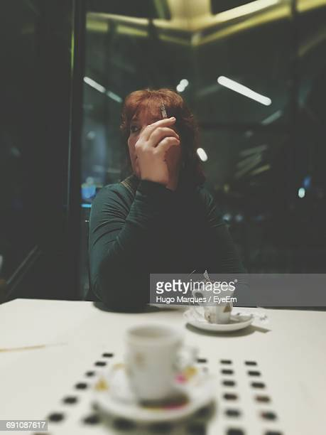 Woman Smoking Cigarette In Illuminated Cafe