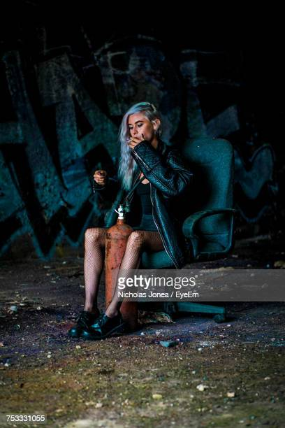 Woman Smoking Cigarette While Sitting On Chair Against Wall