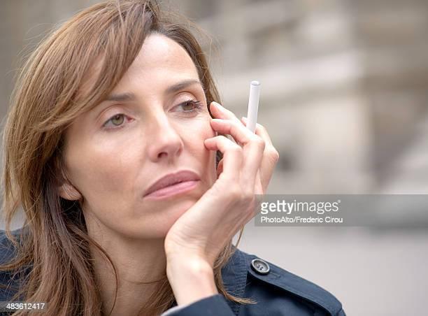 Woman smoking electronic cigarette outdoors