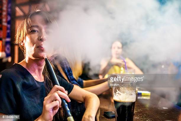 Woman smoking hookah in the bar