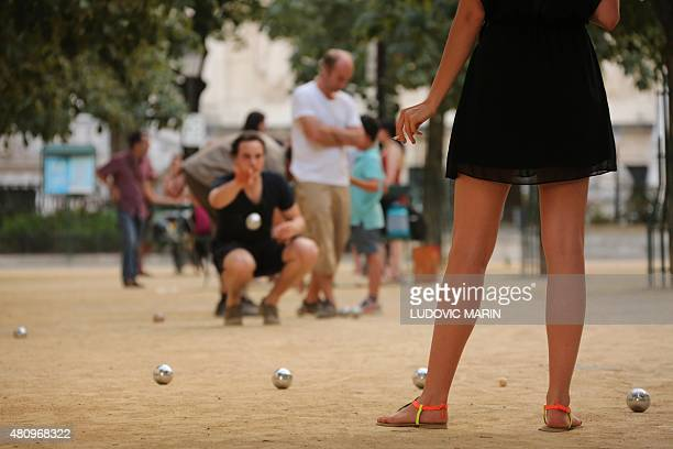 A woman smoking looks at a man launching a petanque boule during a party at the place Dauphine in Paris on July 16 2015 AFP PHOTO / LUDOVIC MARIN