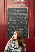 Woman smoking outside of cafe