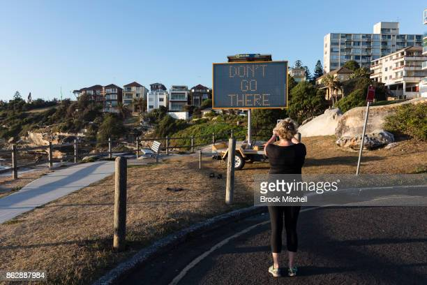 A woman snaps a photo of the work 'Get a Haircut Get a Job' by Karl De Waal at Sculpture By The Sea at Bondi Beach on October 19 2017 in Sydney...