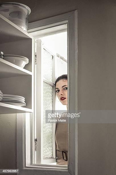 Woman sneak peeking through a window in a kitchen