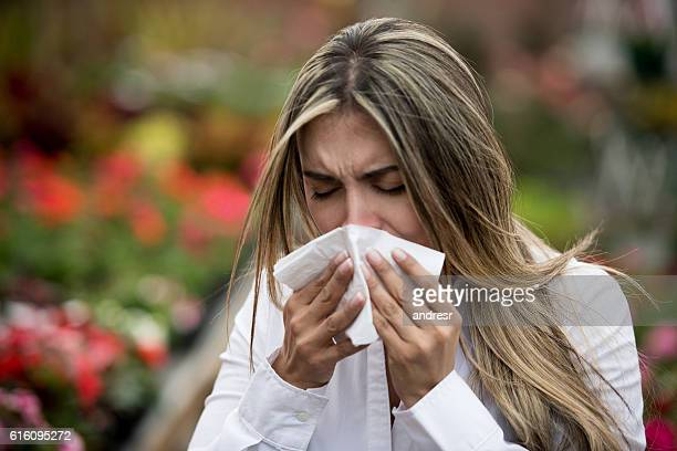 Woman sneezing at a greenhouse