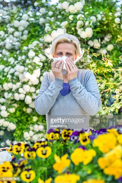 Woman sneezing in the blossoming garden