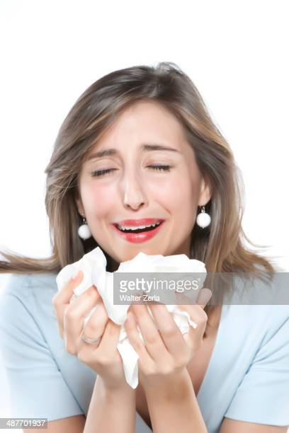 Woman sneezing into tissues
