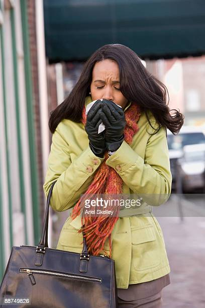 Woman sneezing on sidewalk