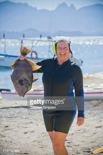woman snorkeler catches fresh trigger fish : Stock Photo