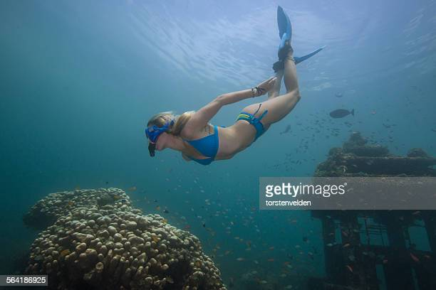 Woman snorkeling and exploring a sunken temple and coral reef, Bali, Indonesia