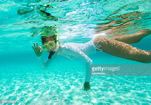 woman snorkeling and showing the O.K. signal underwater