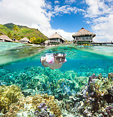 Woman snorkeling in clear tropical waters in front of overwater bungalows. Made of two photos