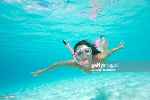 Woman snorkeling in blue clear waters