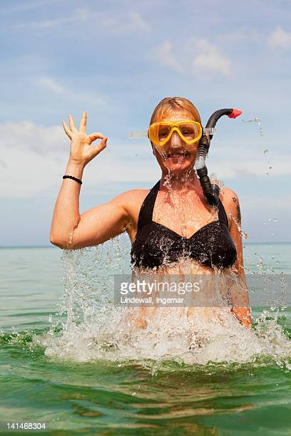 Woman snorkeling in sea showing ok sign with hand