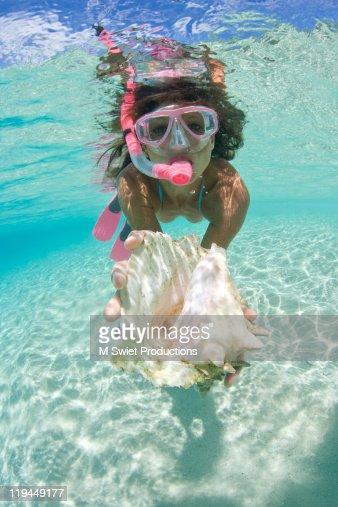 woman snorkeling shell